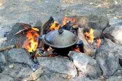 烹调在一个生铁罐的食物在开火,远足 库存图片