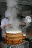 烹调在一个竹火轮的厨师Baozi在街道食物摊位 免版税库存照片