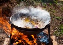 烹调在一口大大锅的肉饭有一强蒸的在开火户外在一个晴朗的夏日 一个水平的框架 免版税库存图片