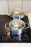 烹调在一现代黑玻璃陶瓷cooktop的罐 免版税库存照片