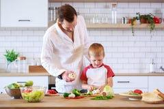 烹调在与菜的桌上的年轻父亲和儿子的图片 免版税图库摄影