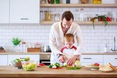 烹调在与菜的桌上的年轻父亲和儿子的图片 免版税库存图片