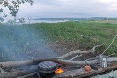 烹调在利益的食物 在河岸的野餐 横向 免版税库存照片