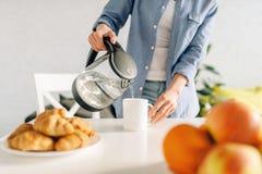 烹调在厨房的愉快的妇女早餐 库存照片