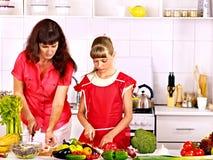 烹调在厨房的母亲和女儿。 图库摄影