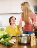 烹调在厨房的母亲和成人女儿 库存照片