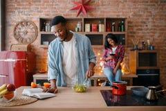 烹调在厨房的黑美国爱夫妇 免版税库存图片