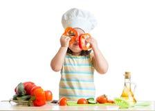 烹调在厨房的滑稽的厨师女孩 免版税库存图片