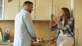 烹调在厨房里和拍照片的有吸引力的夫妇使用在家分享社会媒介的智能手机fo 库存照片