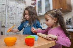 烹调在厨房里的两个可爱的四个岁女孩 免版税库存照片