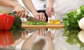 烹调在厨房里的人的手特写镜头  切开新鲜的沙拉的母亲和女儿或者两个女性朋友菜 免版税库存图片