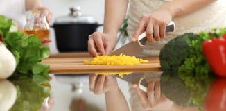 烹调在厨房里的人的手特写镜头  切开新鲜的沙拉的母亲和女儿或者两个女性朋友菜 库存图片