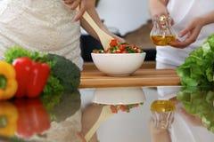 烹调在厨房里的人的手特写镜头  获得的朋友乐趣,当准备新鲜的沙拉时 素食主义者,健康我 免版税图库摄影