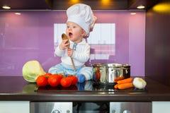 烹调在厨房里的小厨师 库存图片