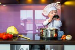 烹调在厨房里的小厨师 免版税库存图片