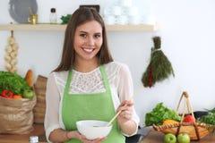 烹调在厨房里的年轻愉快的妇女 健康膳食、生活方式和烹饪概念 早晨好从新鲜开始 免版税图库摄影