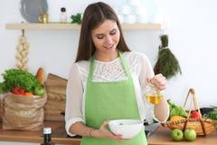 烹调在厨房里的年轻愉快的妇女 健康膳食、生活方式和烹饪概念 早晨好从新鲜开始 免版税库存照片
