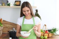 烹调在厨房里的年轻愉快的妇女 健康膳食、生活方式和烹饪概念 早晨好从新鲜开始 免版税库存图片