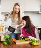 烹调在厨房里的微笑的女孩 免版税图库摄影