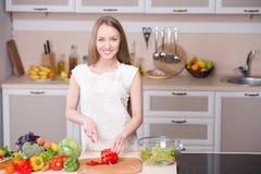 烹调在厨房里的微笑的妇女 库存照片