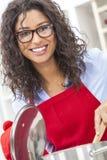 烹调在厨房里的愉快的妇女 免版税库存图片