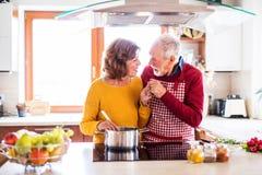 烹调在厨房里的愉快的资深夫妇 免版税库存图片