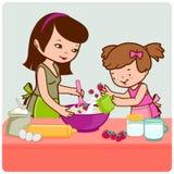 烹调在厨房里的母亲和女儿 免版税库存图片