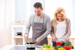 烹调在厨房里的年轻有吸引力的夫妇 库存图片