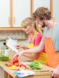 烹调在厨房读书菜谱的夫妇 库存照片