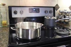 烹调在厨灶的不锈钢罐 免版税库存图片