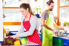 烹调在国内厨房健康食物的夫妇 库存图片