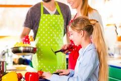 烹调在国内厨房健康食物的家庭 免版税库存图片