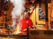 烹调在圣诞节市场的人kebab在晚上 库存照片