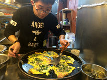 烹调在地方样式的一个年轻人牡蛎在一家餐馆在厦门市,中国 库存照片