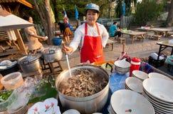 烹调在大平底深锅的厨师鸡腿在街道市场的全国盘的 库存照片
