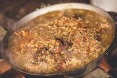 烹调在大锅的plov 仅肉、葱和红萝卜在大锅 野外用的全套炊具 东部的烹调 库存照片