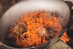 烹调在大锅的plov 仅肉、葱和红萝卜在大锅 野外用的全套炊具 图库摄影