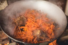 烹调在大锅的plov 仅肉、葱和红萝卜在大锅 野外用的全套炊具 免版税图库摄影