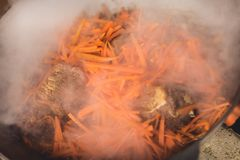烹调在大锅的plov 仅肉、葱和红萝卜在大锅 野外用的全套炊具 免版税库存照片