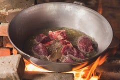 烹调在大锅的plov 仅肉和葱在大锅 野外用的全套炊具 图库摄影