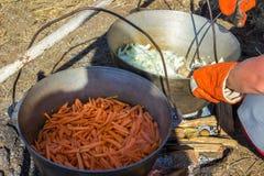 烹调在大锅的plov 在大锅的仅肉 野外用的全套炊具 东部的烹调 免版税库存图片