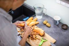 烹调在她的现代厨房里的少妇 库存照片
