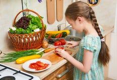 烹调在家庭厨房里的儿童女孩,砍蕃茄 菜和新鲜水果篮子在厨房内部 健康食物骗局 库存图片