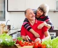 烹调在家庭厨房里的愉快的年长夫妇 免版税库存照片