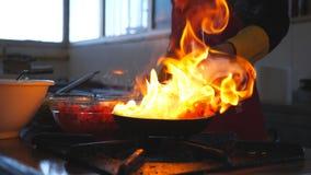 烹调在平底锅的无法认出的厨师鲜美flambe样式盘餐馆的访客的 混合专业的厨师和 影视素材