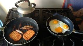 烹调在我的火炉马铃薯煎饼、香肠和鸡蛋的早餐 免版税库存照片