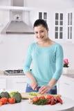 烹调在新的厨房里的妇女做与蔬菜的健康食物 免版税库存图片