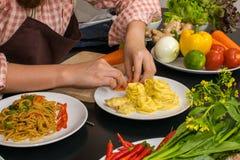 烹调在新的厨房里的美丽的妇女做健康食物与 免版税库存照片