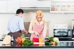 烹调在时髦和现代厨房里的夫妇 免版税库存照片