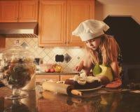 烹调在有厨师帽子的厨房里的孩子 库存图片